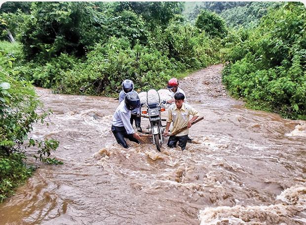 Men pulling bike from river
